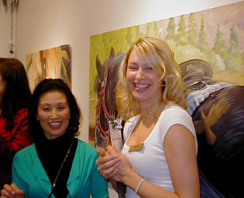 Artist: Gallery Event Photos, Title: Gallery Asst. Carrie, tells Masami Olsen that she has a horse just like the one behind them. - click for larger image